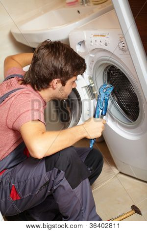 Young attractive worker in uniform fixing washing machine, background