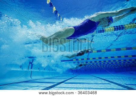 Female participants swimming underwater during a swimming race