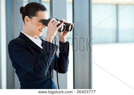 young pretty businesswoman looking outside office window with binoculars