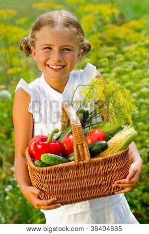Harvests of vegetables - lovely girl with the basket of ecological harvests