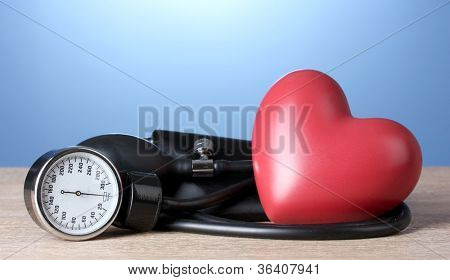Black tonometer and heart on wooden table on blue background