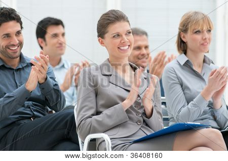 Happy business group of people clapping hands during a meeting conference