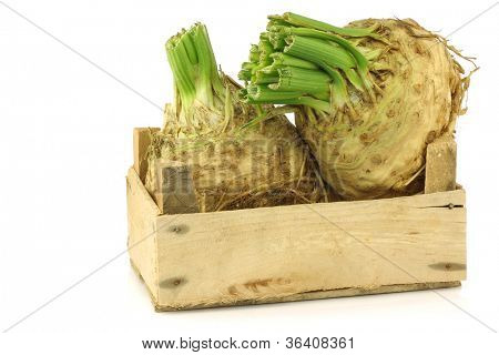 fresh celery roots with some foliage in a wooden crate on a white background