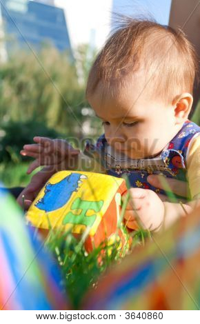 Baby Lying In The Grass And Playing With Blocks
