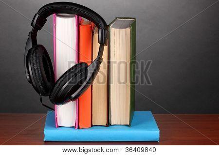 Headphones on books on wooden table on black background