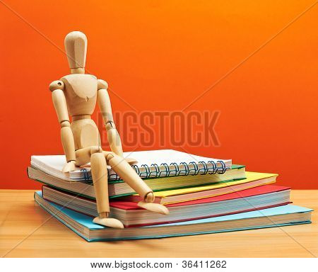 Back to School Series: wooden man sitting over stack of colorful books on the classroom desk