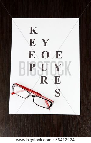 Eyesight test chart with glasses on wooden background close-up