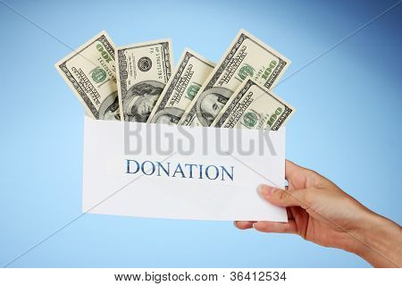 Woman's hand holding an envelope with money on blue background