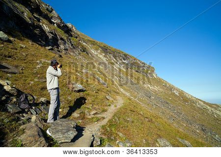 Young Tourist Taking Photos Outdoor In The Mountain Landscape