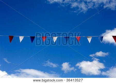 Decorative bunting under blue sky.