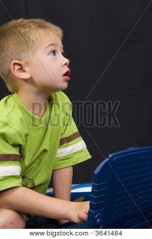 Little Boy Playing On Black Background