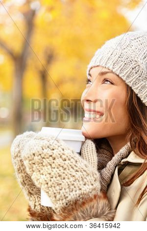 Autumn woman drinking coffee. Fall concept of young woman enjoying hot drink from disposable coffee cup in fall landscape. Serene happy mixed race Asian / Caucasian female model  in city forest park.