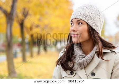 Fall woman portrait of woman looking sideways smiling serene. Beautiful young multiracial woman walking in autumn in city forest park in trench coat.