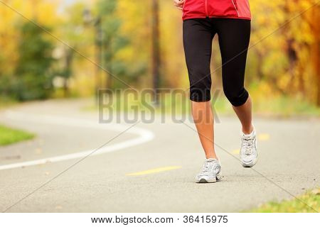 Runner legs and running shoes. Woman jogging in fall colors on forest path.