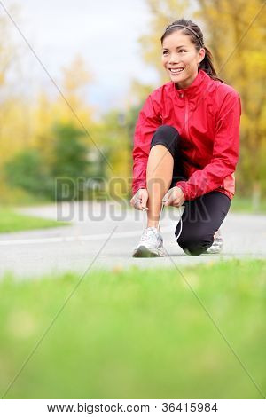 Runner woman tying running shoes outside in fall. Beautiful young fitness model smiling happy in casual jogging clothing.