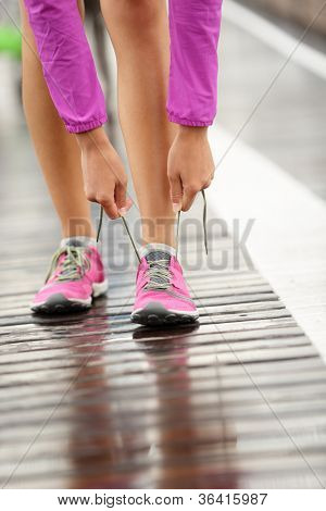 Running shoes. Barefoot running shoes closeup. Woman tying laces before jogging in minimalistic barefoot running shoes on Brooklyn Bridge, New York, USA.