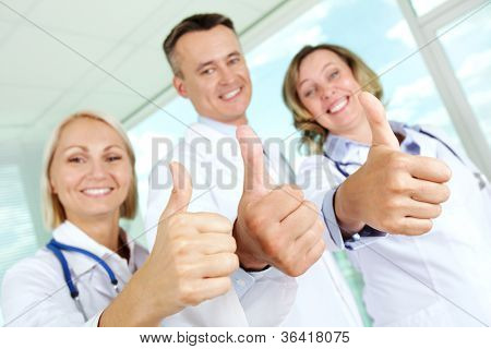 Three clinicians in white coats keeping thumbs up and looking at camera