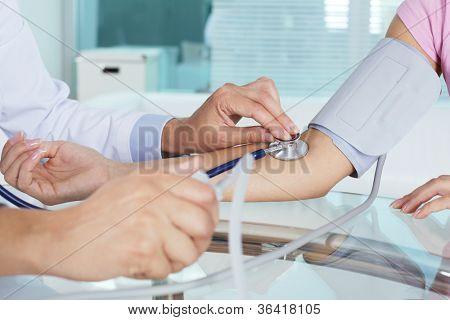 Close-up of patient�?�¢??s arm during blood pressure measuring at medical consultation