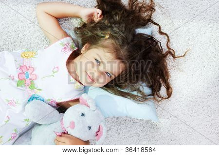 Portrait of lovely girl lying with teddybear