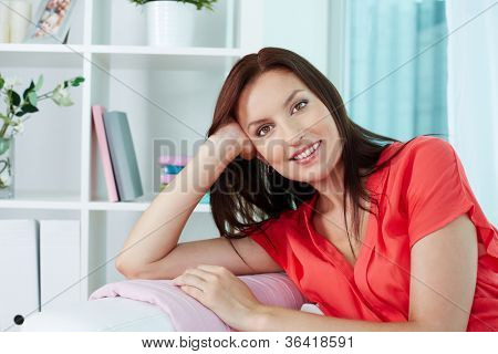 Portrait of a smiling woman looking at camera while resting at home