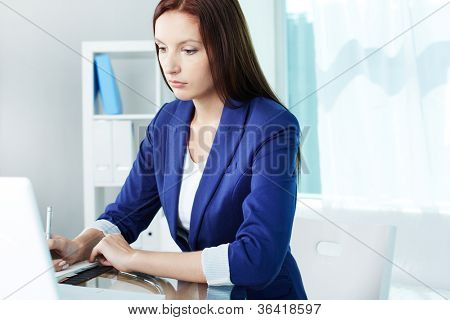Business lady making notes while looking at laptop screen