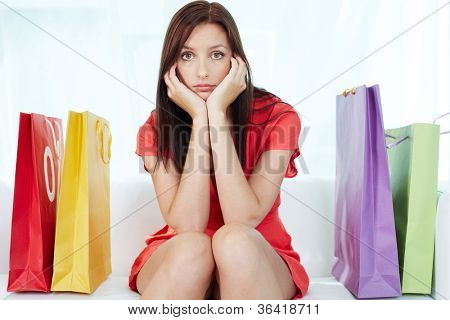 Portrait of young stressed brunette surrounded by paperbags