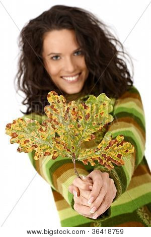 Autumn tree leaf and smiling woman, closeup hand and selective focus.