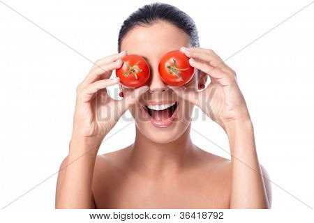 Healthy young woman holding tomatos over her eyes, laughing, bare shoulders.
