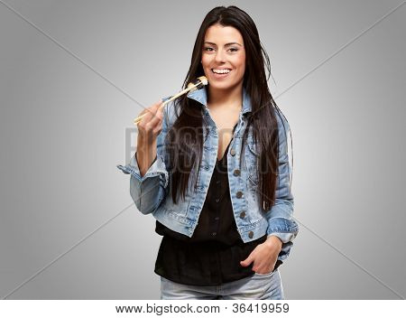 Young Woman Holding A Piece Of Sushi With Chopsticks On Grey Background