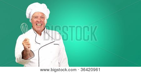 Portrait Of A Senior Male Chef Holding A Beater On Green Background