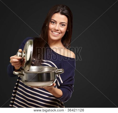 Female Holding A sauce pan As A Telephone On A Black Background
