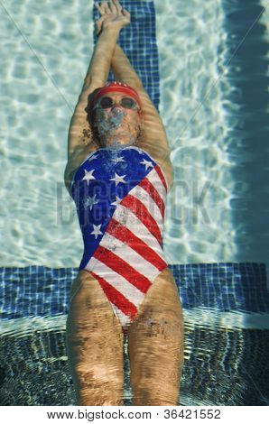 High angle view of female participant in an American swimsuit swimming in backstroke