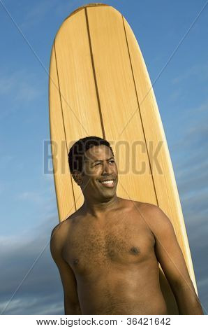 An African American man with surfboard standing over sky
