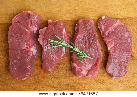 Boneless lamb leg steaks on wooden chopping board.