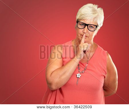Senior Woman With Finger On Lips Isolated On Pink Background