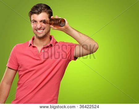 man looking inside an empty bottle isolated on green background