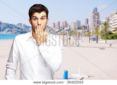 portrait of young man surprised against a beach