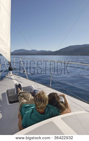 Rear view of a couple relaxing on a sailboat