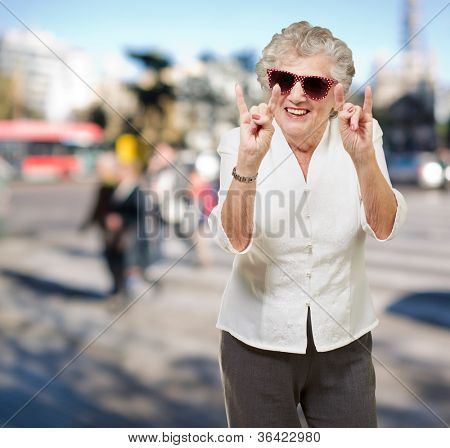 portrait of a happy senior woman doing rock symbol at crowded street