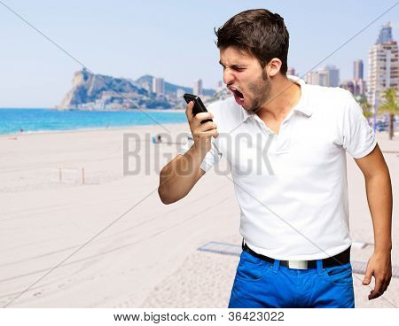 portrait of young man arguing against a beach