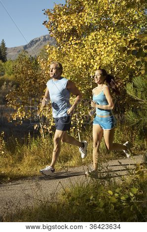 Man and woman jogging on a path in the forest