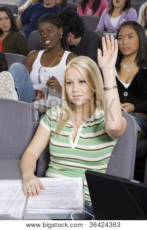Young female student raising her hand to answer