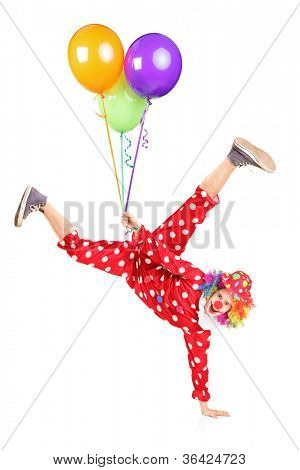 Clown holding balloons and standing on one hand isolated on white background