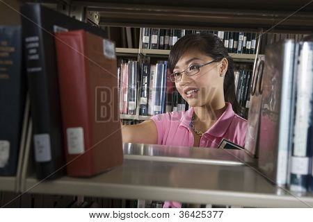Young Asian woman looking out for a book from the shelf in the library