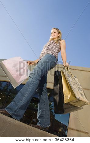 Low angle view of young woman carrying shopping bags in front of store