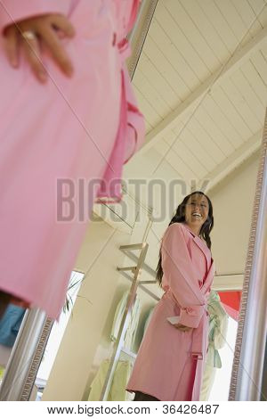Low angle view of happy young woman trying overcoat in front of mirror at store