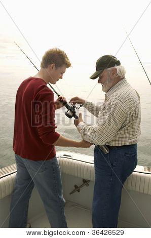 Senior man with grandson fishing on yacht