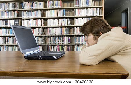 Side view of a bored male college student sitting at library desk looking at laptop