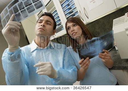 Mature doctor looking at tooth x-ray with colleague holding other x-ray