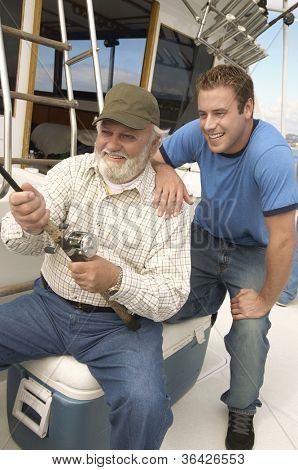 Glücklicher Alter Mann mit Enkel gemeinsam Fischen auf yacht